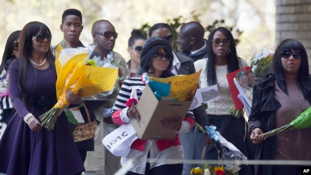 A group of unidentified relatives carry bunches of flowers that were left by wellwishers into the Mediclinic Heart Hospital where former South African President Nelson Mandela is being treated in Pretoria, South Africa, June 27, 2013.