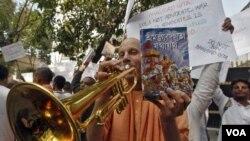 Seorang anggota sekte global Hare Krishna memainkan terompetnya selama protes di luar konsulat Rusia di Kolkata (19/12). Parlemen India dan pengunjuk rasa berkumpul di luar konsulat Rusia menentang pelarangan kitab Bhagavad Gita.