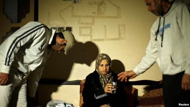 Suhad al-Katib, a Palestinian woman patient who suffers cancer holds a glass of water as she sits at her house after she was not allowed to enter Israel, in Gaza City, Feb. 12, 2014.
