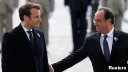 에마뉘엘 마크롱(왼쪽) 프랑스 대통령 당선인이 8일 프랑수아 올랑드 대통령과 함께 파리 시내 무명용사비에 헌화하면서 눈을 맞추고 있다.
