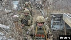 Sejumlah anggota pasukan keamanan Ukraina berjalan di perbatasan yang memisahkan dengan para pemberontak pro Rusia dekat Donetsk, Ukraina, 11 April 2021.