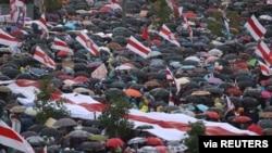 Para pedemo berlindung di bawa payung-payung dalam demo oposisi menentang hasil pilpres, di Minsk, Belarusia, 6 September 2020.