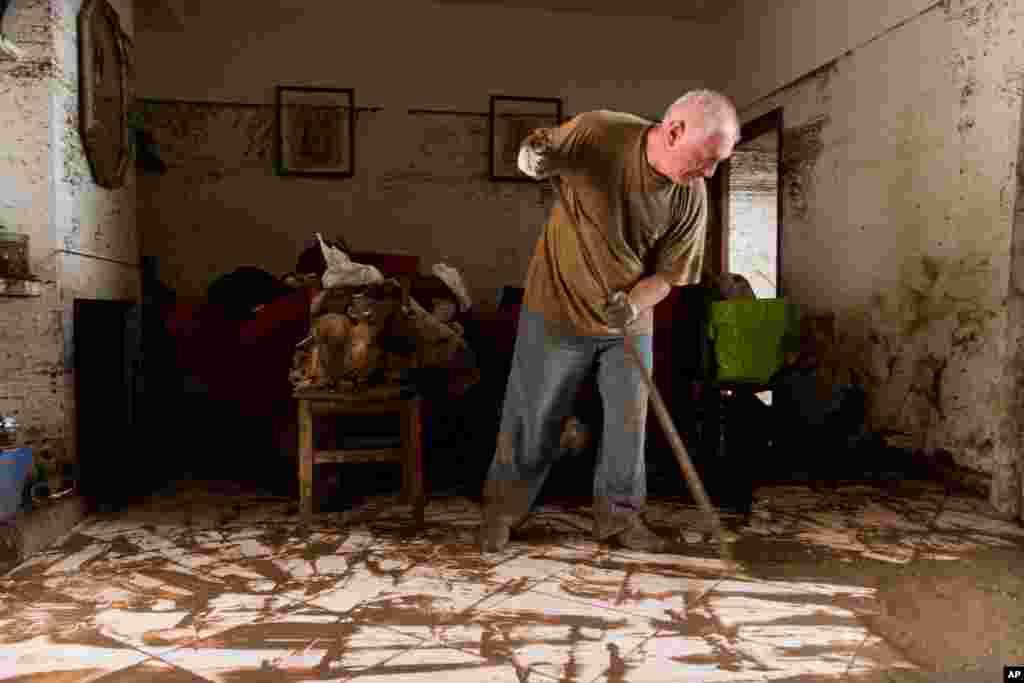 스페인 팔마에서 동쪽으로 40 마일 떨어진 지역에 폭우가 내린 후 남성이 집을 청소하고 있다.
