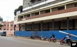 Moto-táxis, principal ocupação dos jovens, passam em frente a um prédio de Malanje