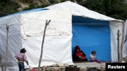 FILE - Internally displaced refugees rest near their tents in Rihaniyya camp in northern Syria's Latakia province, May 2, 2015. Six died in a June 1 fire at another camp in Lebanon.