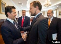 Presiden Meksiko Enrique Pena Nieto (L) berjabat tangan dengan aktor Leonardo DiCaprio sebagai konglomerat Carlos Slim (R) dalam sebuah pertemuan untuk menandatangani nota kesepahaman (MoU) yang bertujuan melindungi ekosistem laut di Teluk California, di kediaman Presiden di Los Pinos, Mexico City, 7 Juni 2017. (Foto:Reuters/Mexican Presidency)