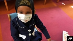 Amira Hassan, of Burnsville, Minnesota, plays in the waiting room at the specialty clinic at Children's Minnesota in Minneapolis, Minnesota, May 2, 2017. Amira went to the hospital's clinic for a routine wellness check, but had to wear a mask to protect her from measles after an outbreak.