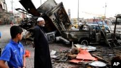Warga Irak mengamati puing-puing akibat bom mobil di Sadr City, Iraq (11/4). (AP/Karim Kadim)