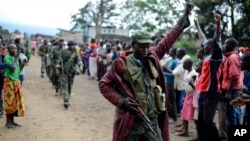 FILE - A Congolese army soldier responds to cheers from civilians as the army enters the town of Bunagana, eastern Congo, near the border with Uganda, Oct. 30, 2013.