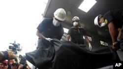 Cảnh sát khiêng thi thể một bệnh nhân ra khỏi trung tâm phục hồi bị hỏa hoạn ở ngoại ô Lima, ngày 5/5/2012