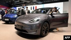 People look at a Tesla Model Y car at a Tesla showroom in Beijing on January 5, 2021. (Photo by WANG Zhao / AFP)