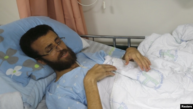 FILE - Palestinian journalist Mohammed al-Qeq, 33, who had been on hunger strike to protest his administrative detention in an Israeli jail, is seen at Haemek hospital in the northern Israeli city of Afula, Feb. 5, 2016.  His family says he's ending his fast and will be released in three months' time.