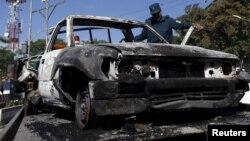 2015年5月27日阿富汗警察检查塔利班袭击后汽车残骸