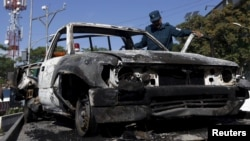 An Afghan policeman inspects the wreckage of a car after a Taliban attack on a guesthouse in Kabul, May 27, 2015.