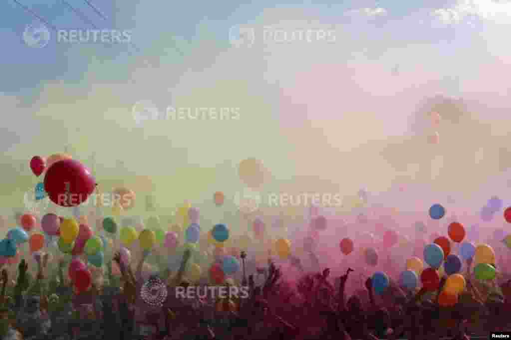 Participants throw colored powders as they take part in the Color Run in the Andalusian capital of Seville, Spain. The Color Run is a five-kilometer race, held in cities across the U.S. and world, to promote healthy living, and to benefit a charity chosen by the race's local organizers.
