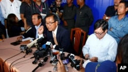 Cambodia National Rescue Party President Sam Rainsy, center, speaks during a press conference in his main party headquarters in Chak Angre Leu in Phnom Penh, Cambodia, July 29, 2013.