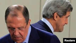 U.S. Secretary of State John Kerry (R) walks behind Russian Foreign Minister Sergei Lavrov (L) at the start of a NATO-Russia foreign ministers meeting in Brussels, April 23, 2013.