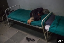 FILE - A Kashmiri patient suffering from symptoms of schizophrenia lies on a bed and periodically shouts to medical staff after being brought by relatives to the casualty ward at the Psychiatric Diseases hospital in Srinagar, Nov. 20, 2015.