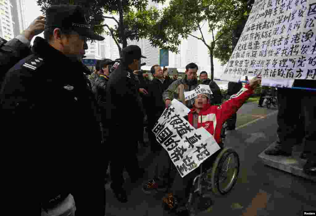 A supporter of the Southern Weekly newspaper in a wheelchair chants slogans in front of police officers near the newspaper's office in the southern Chinese city of Guangzhou, January 10, 2013.
