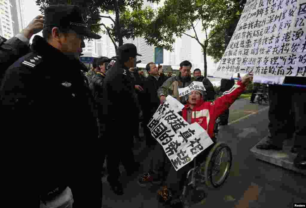 2013年1月10日,一位坐轮椅的《南方周末》支持者在广州《南周》总部附近在警察面前呼喊口号。他随后被便衣警察带走。