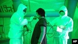 星期三﹐日本醫務人員正檢查這名婦女是否受到核輻射