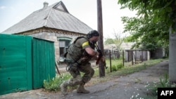 Ukrainian serviceman holds a gun during fighting in Mariinka, in the region of Donetsk, June 4, 2015.