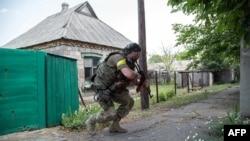 Ukrainian serviceman holds a gun during fighting in Mariinka, in the region of Donetsk, June 4, 2015.