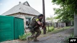Tentara pemerintah Ukraina mengusung senjata di Marinka, Donetsk.