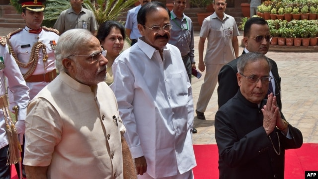 Indian President Pranab Mukherjee (R) arrives with Indian Prime Minster Narendra Modi (L) to address the joint session of Parliament in New Delhi, June 9, 2014.