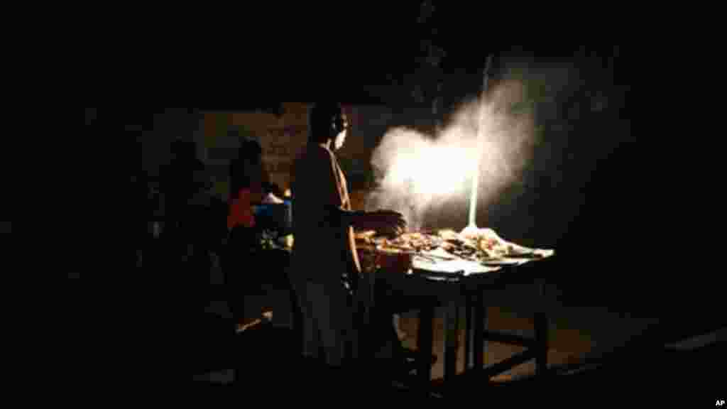 A man cooks suya, a local spicy meat dish.