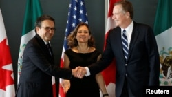 Mexico's Economy Minister Ildefonso Guajardo, left, shakes hands with U.S. Trade Representative Robert Lighthizer before the start of a trilateral meeting with Canada's Foreign Minister Chrystia Freeland during the third round of NAFTA talks in Ottawa, Ontario, Canada, Sept. 27, 2017.