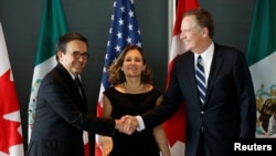 FILE - Mexico's Economy Minister Ildefonso Guajardo, left, shakes hands with U.S. Trade Representative Robert Lighthizer before the start of a trilateral meeting with Canada's Foreign Minister Chrystia Freeland during the third round of NAFTA talks in Ottawa, Ontario, Sept. 27, 2017.