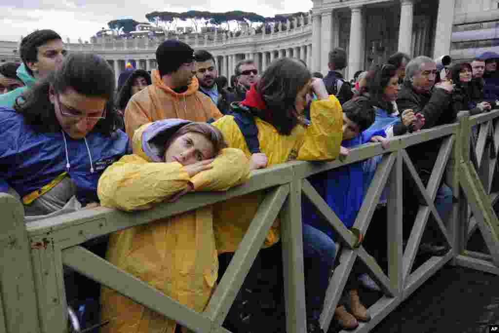 Visitors wait in Saint Peter's Square during the second day of voting by cardinals to elect a new pope at the Vatican, March 13, 2013.