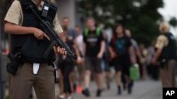 La police escorte quelques personnes qui quittent le centre commercial Olympia après une fusillade, à Munich, Allemagne, 22 juillet 2016.