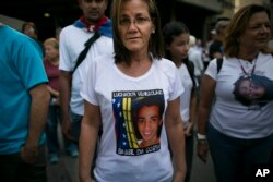 Jineth Frias poses for a photo in a T-shirt featuring her slain son, Bassil da Costa, at an anti-government protest marking the third anniversary of his killing by security forces during weeks of unrest in Caracas, Venezuela, Feb. 12, 2017.