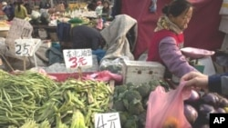 A customer picks up a plastic bag of peppers he bought at a fruit and vegetable market in Beijing, 17 Nov 2010