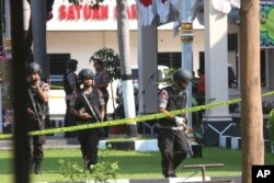 FILE - Members of a police bomb squad examine the area where a suicide bomber blew himself up at the local police headquarters in Solo, Central Java, Indonesia, July 5, 2016. Police said the bomber was a friend of Bahrun Naim, one of the hundreds of Indonesians with IS in Syria and who has been linked to other plots in Indonesia.