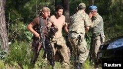 Binh lính Thổ Nhĩ Kỳ bắt giữ sĩ quan Erkan Cikat, người bị tình nghi tham gia vào vụ đảo chính bất thành, tại Marmaris, Thổ Nhĩ Kỳ, ngày 25 tháng 7 năm 2016.