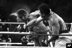 FILE - George Foreman takes a right to the head from challenger Muhammad Ali in the seventh round of the match dubbed the Rumble in the Jungle in Kinshasa, D.R.C., Oct. 30, 1974.