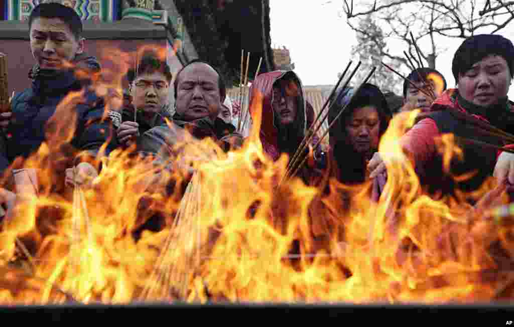 People burn incense to pray for good fortune on the first day of the Chinese Lunar New Year at Yonghegong Lama Temple in Beijing. The Lunar New Year, or Spring Festival, begins on January 23 and marks the start of the Year of the Dragon, according to the