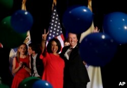 New Jersey gubernatorial nominee Phil Murphy, right, and Lt. Gov. nominee Sheila Oliver wave to supporters as balloons drop during their election night victory party at the Asbury Park Convention Hall, Nov. 7, 2017, in Asbury Park, New Jersey.