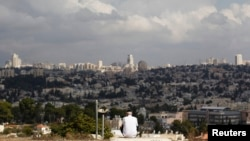 A view of Jerusalem is seen in the background as a man sits in Giv'at HaMatos, a neighborhood on the southern fringes of Jerusalem's city limits where Israel has decided to move forward on a settler housing project, Oct. 2, 2014.
