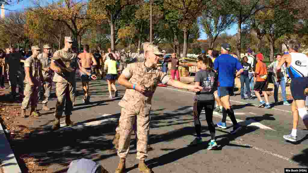 Marines hand out Jelly Belly Sports Beans near the mile 19 mark of the Marine Corps Marathon on Sunday in Washington, D.C.