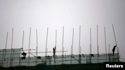 FILE - Laborers work at a construction site in Beijing.