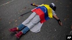 Un manifestante cubierto con la bandera venezolana yace en el suelo durante una protesta contra la violencia en Caracas.