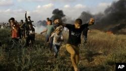 Palestinski demonstranti traže zaklon od suzavca koji su ispalile izraelske snage, dok drugi pale gume u blizini granice Pojasa Gaze i Izraela, tokom protesta istočno od Kan Junisa, u Pojasu Gaze, 1. juna 2018.