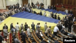 Opposition deputies cover their seats with gigantic national flags to protest against a draft law on languages, which was scheduled to be discussed during a session in the Ukrainian parliament in Kiev
