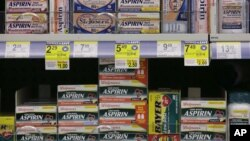 FILE - Packages of aspirin fill the shelves of a drugstore, Aug. 11, 2009.