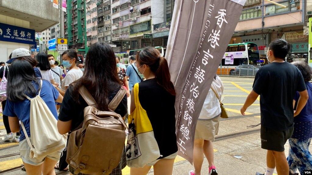 """香港言語治療師總工會主席黎雯齡(手持旗幟者)與兩名成員,今年7-1在港島銅鑼灣及灣仔一帶做""""流動街站"""",呼籲市民繼續發聲,爭取民主 (美國之音/湯惠芸)"""