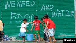 Children help to carry pails of drinking water as they walk past graffiti calling for help after Typhoon Haiyan devastated Tacloban city, central Philippines, Nov. 12, 2013.